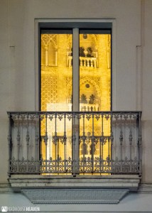 The Cathedral of Seville has a golden reflection in the polished windows of the residential building facing it