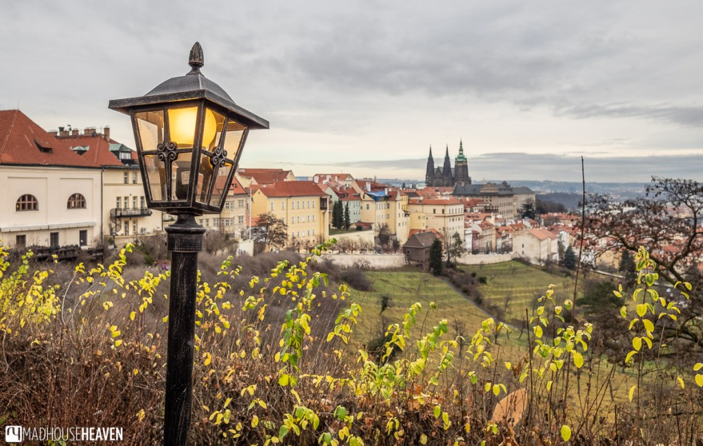 A yellow lamp, lit during a grey winter's day. The Prague Castle grounds in the background.