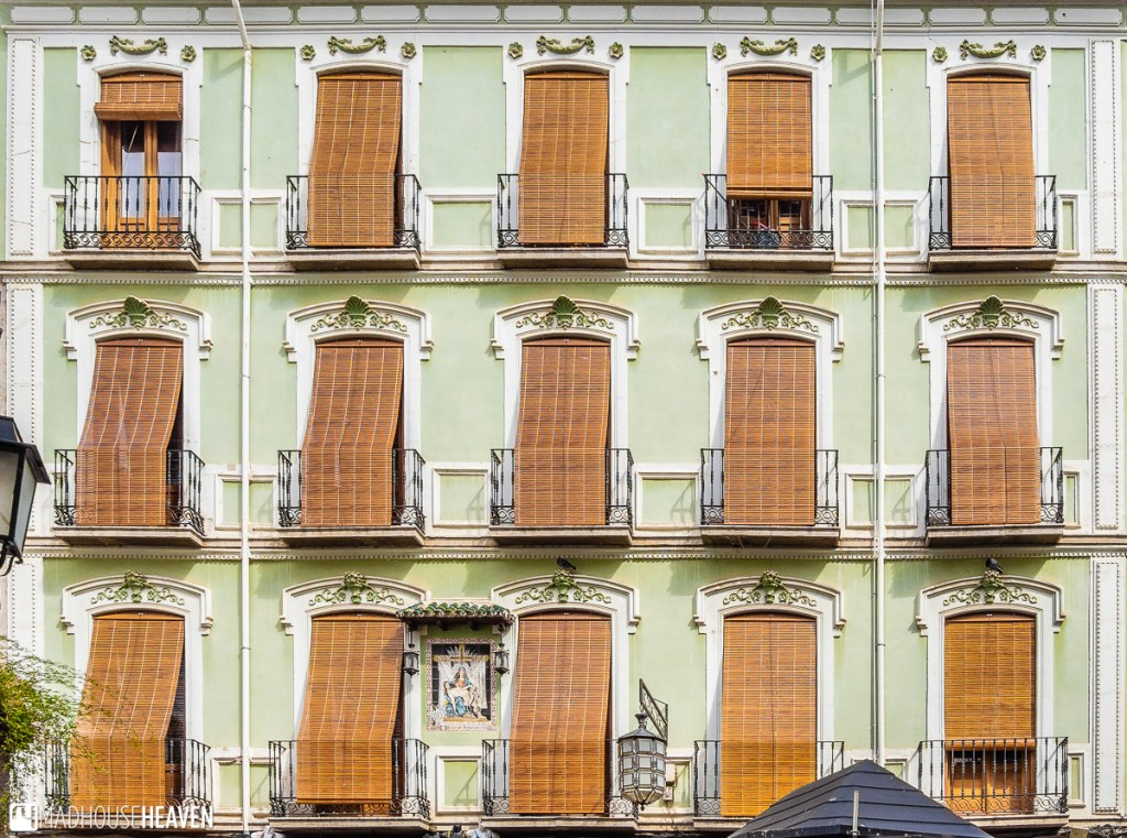 A colourful facade with many windows in the streets of Granada