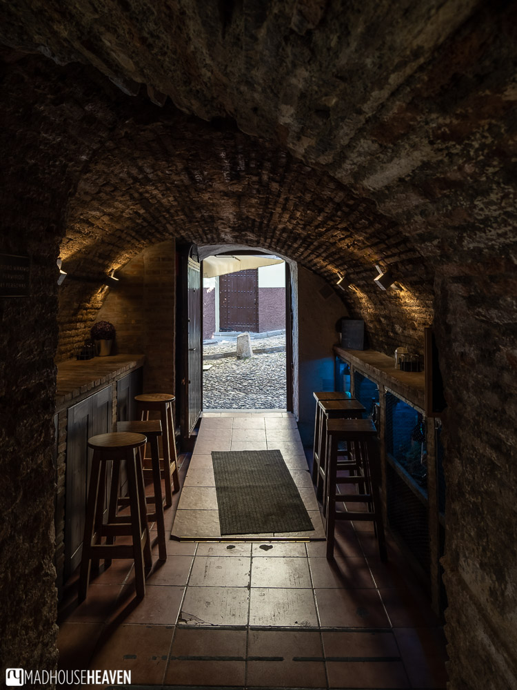 A cellar-like restaurant with bar tables against the curved stone walls