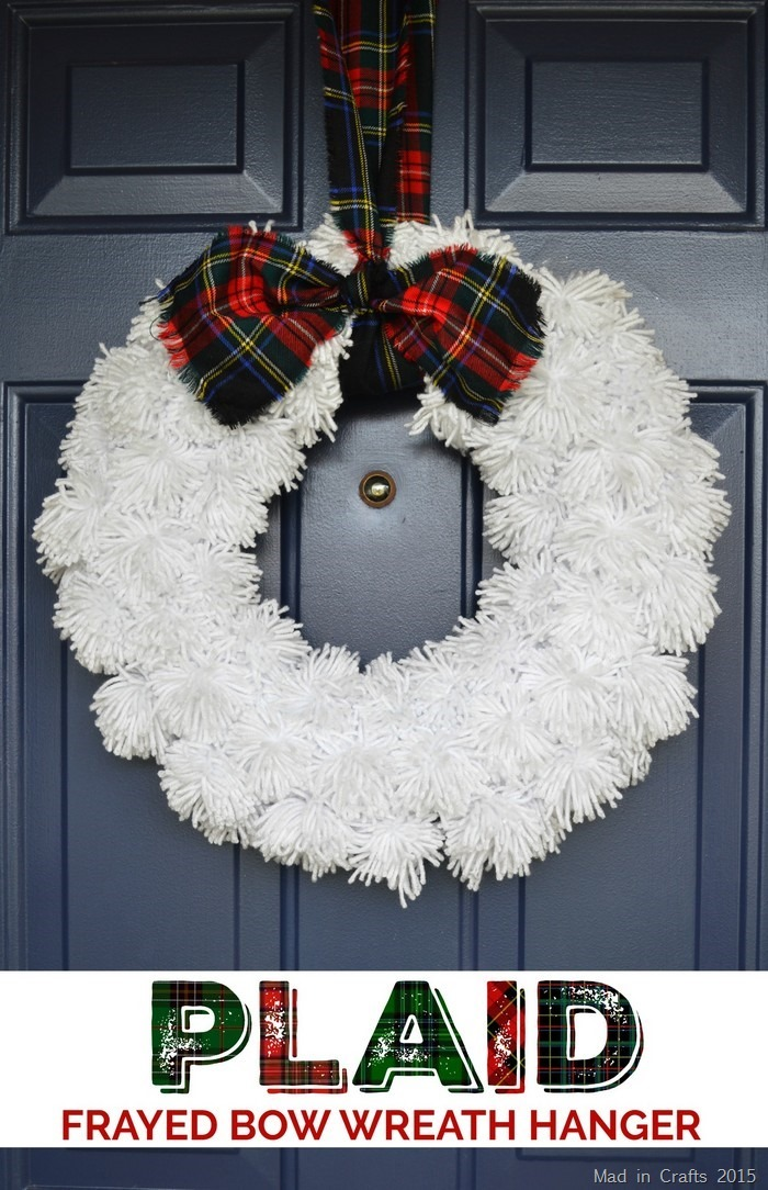 White yarn wreath with plaid ribbon hanging on a blue front door