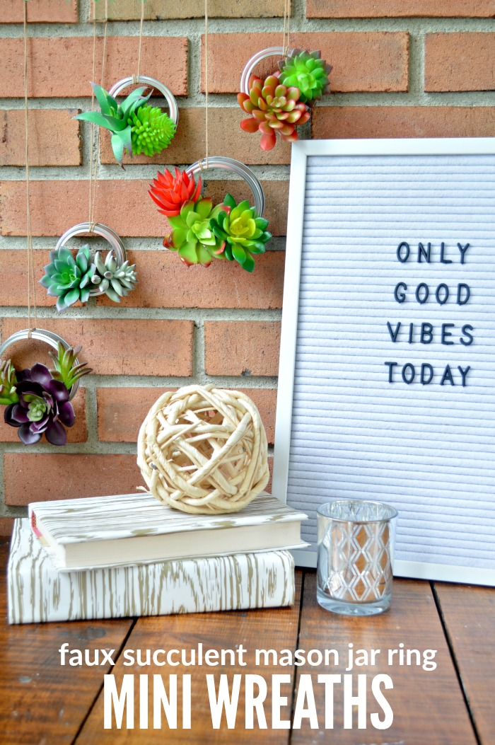 Mason jar ring succulent wreaths hanging next to a letterboard that says Only Good Vibes Today