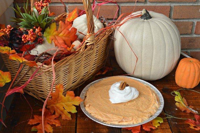 pumpkin cream pie next to a pumpkin and fall leaves