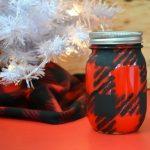 red and black buffalo check painted mason jar next to a white christmas tree