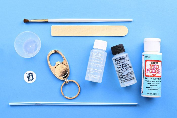 Resin supplies and a bottle opener key chain blank on a blue background