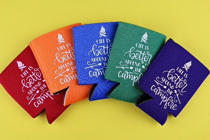 colorful can koozies with iron on vinyl on a yellow background