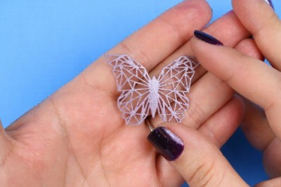 hands holding a small geometric butterfly embellishment made from liquid sculpey