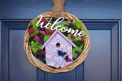 welcome wreath with reindeer moss and a birdhouse on a blue door