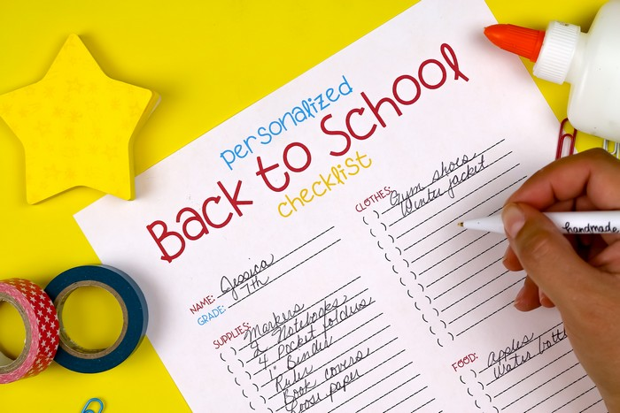 hand writing on a Back to School Checklist printable on a yellow background with school supplies