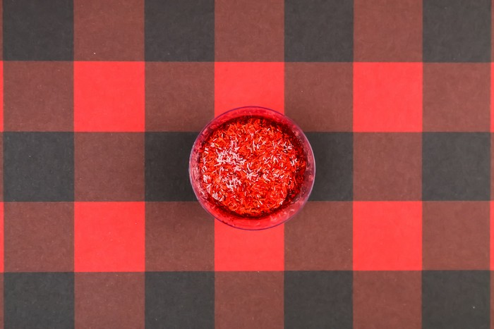 glittery resin in a small cup on a plaid background