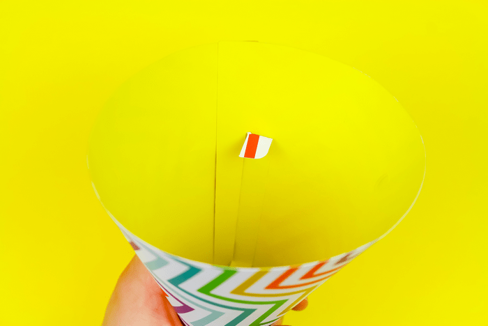 hand assembling a colorful paper party hat