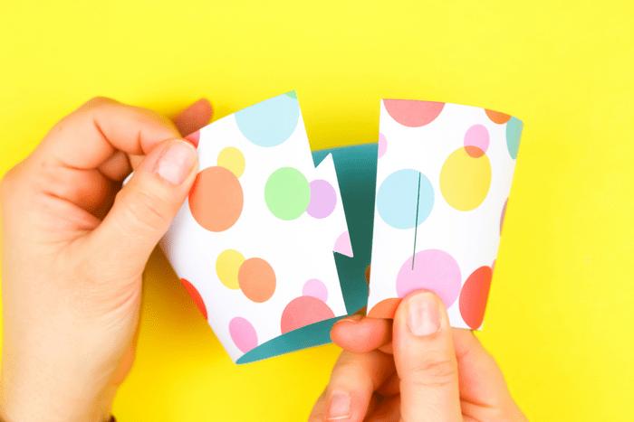hands assembling a polka dot cupcake wrapper