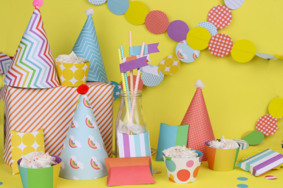 Colorful DIY paper party supplies on a yellow background
