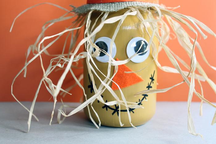 scarecrow painted mason jar on an orange background