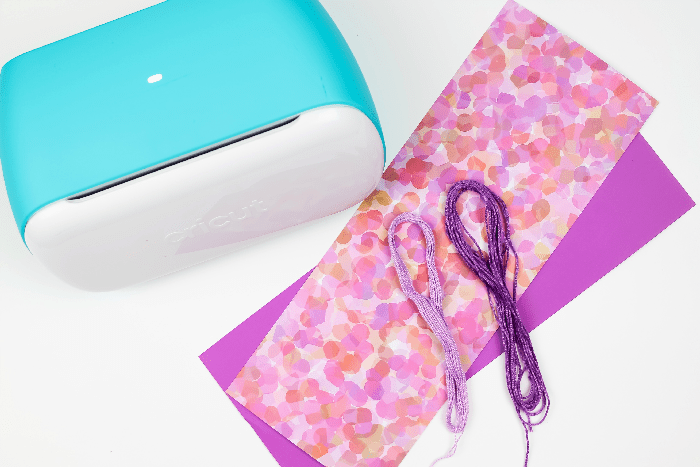 Materials for making adhesive cricut joy paper bookmarks on a white background