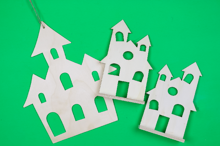 unpainted wooden halloween houses on a green background