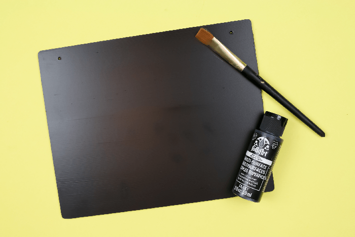 Black sign with paint and paintbrush on a yellow background