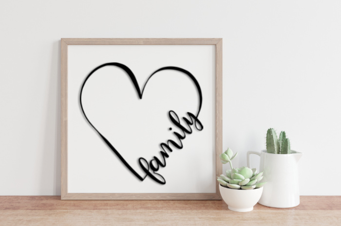 Family heart SVG design in a wood frame next to succulents