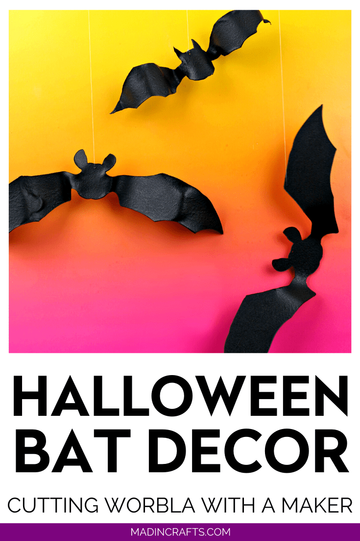 hands holding black bat shape cut out of plastic on orange and pink background