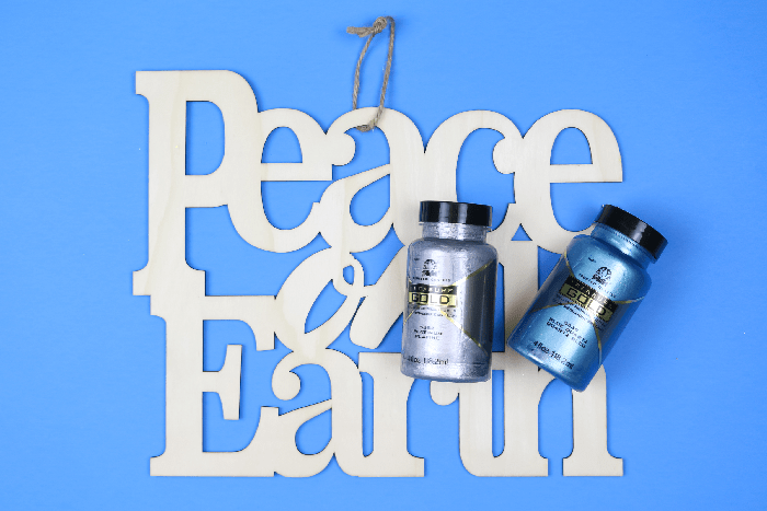 unpainted wood Peace on Earth sign with bottles of paint on a blue background
