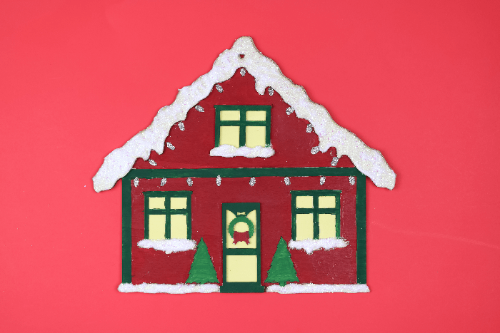 Painted Christmas house sign on a red background