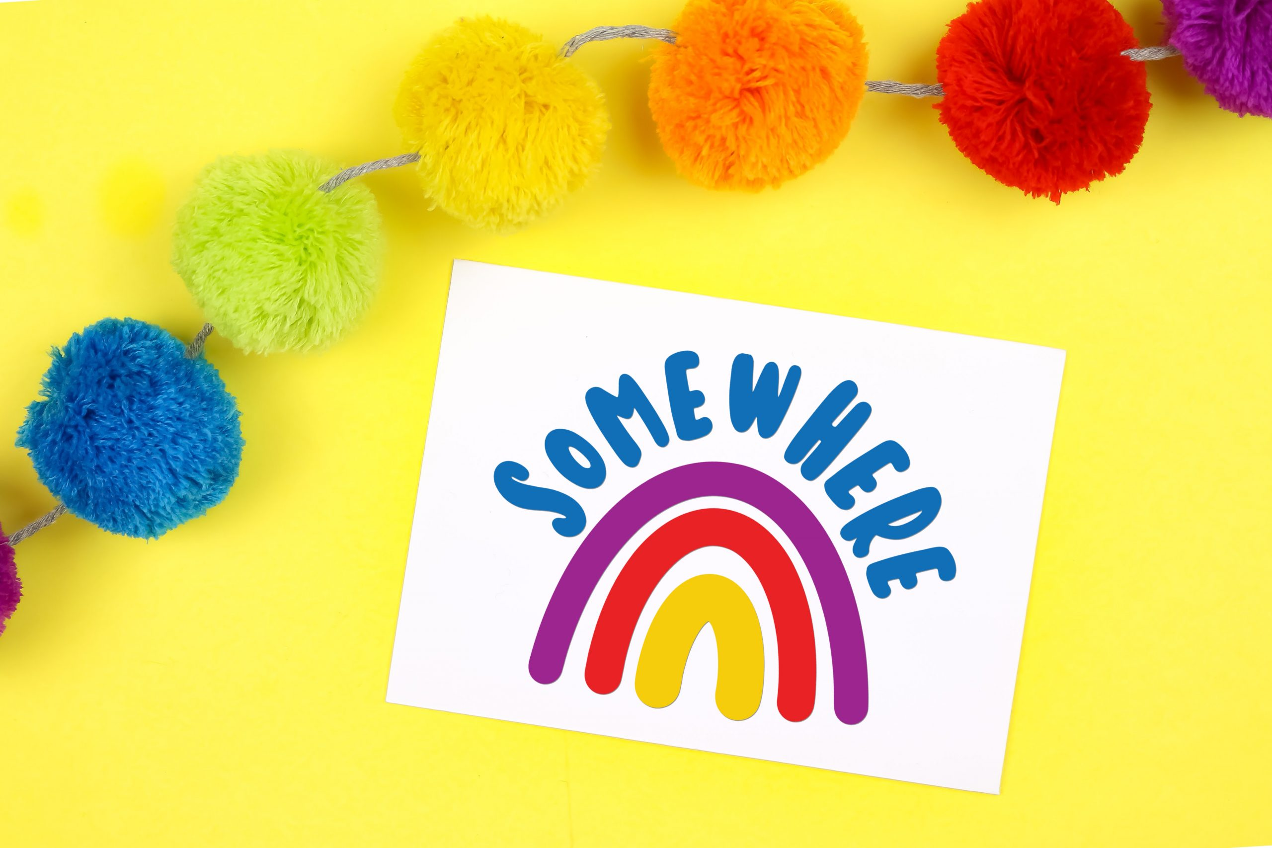 Colorful rainbow card on a yellow background with rainbow pom garland
