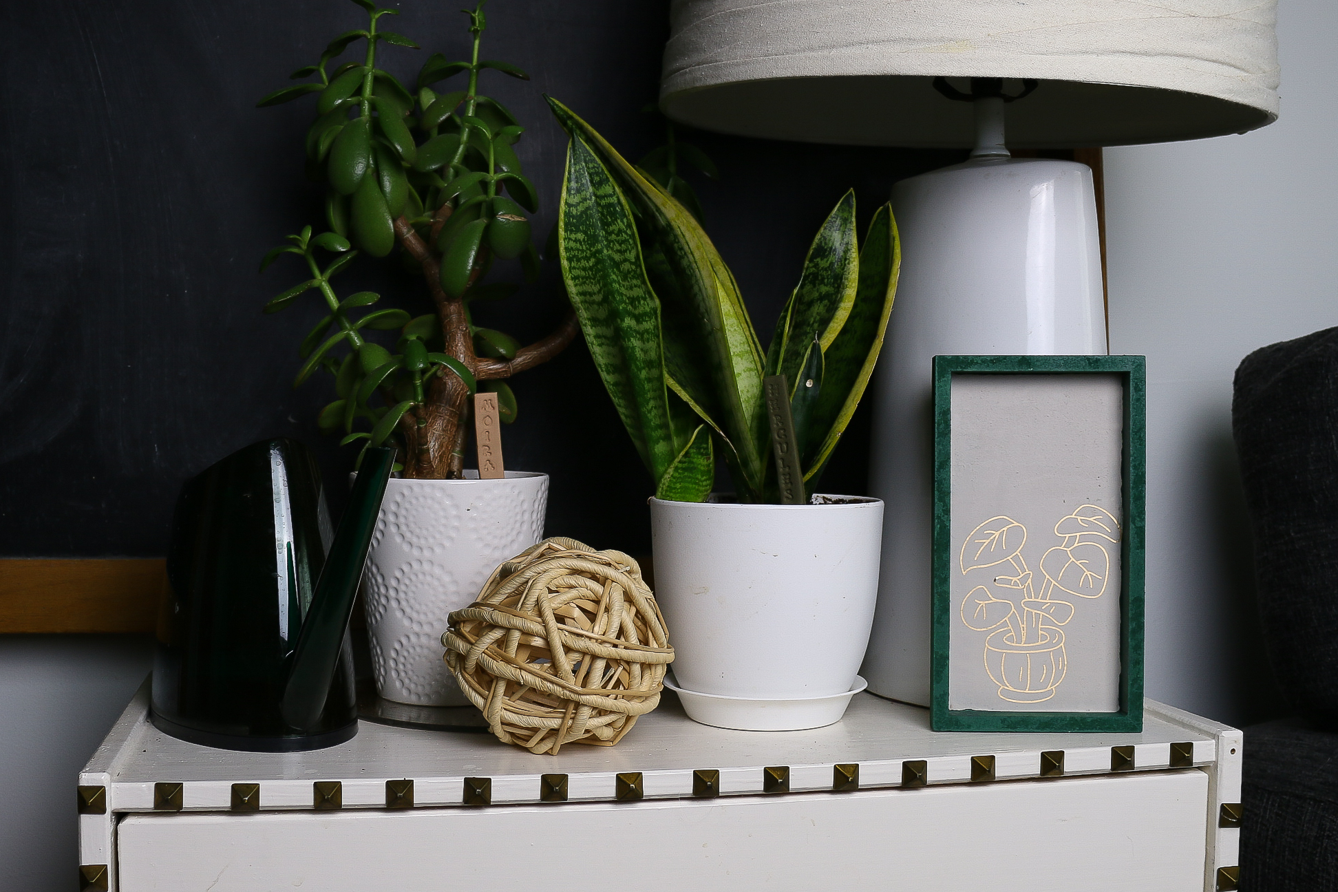 a sidetable with plants and a framed piece of plant artwork
