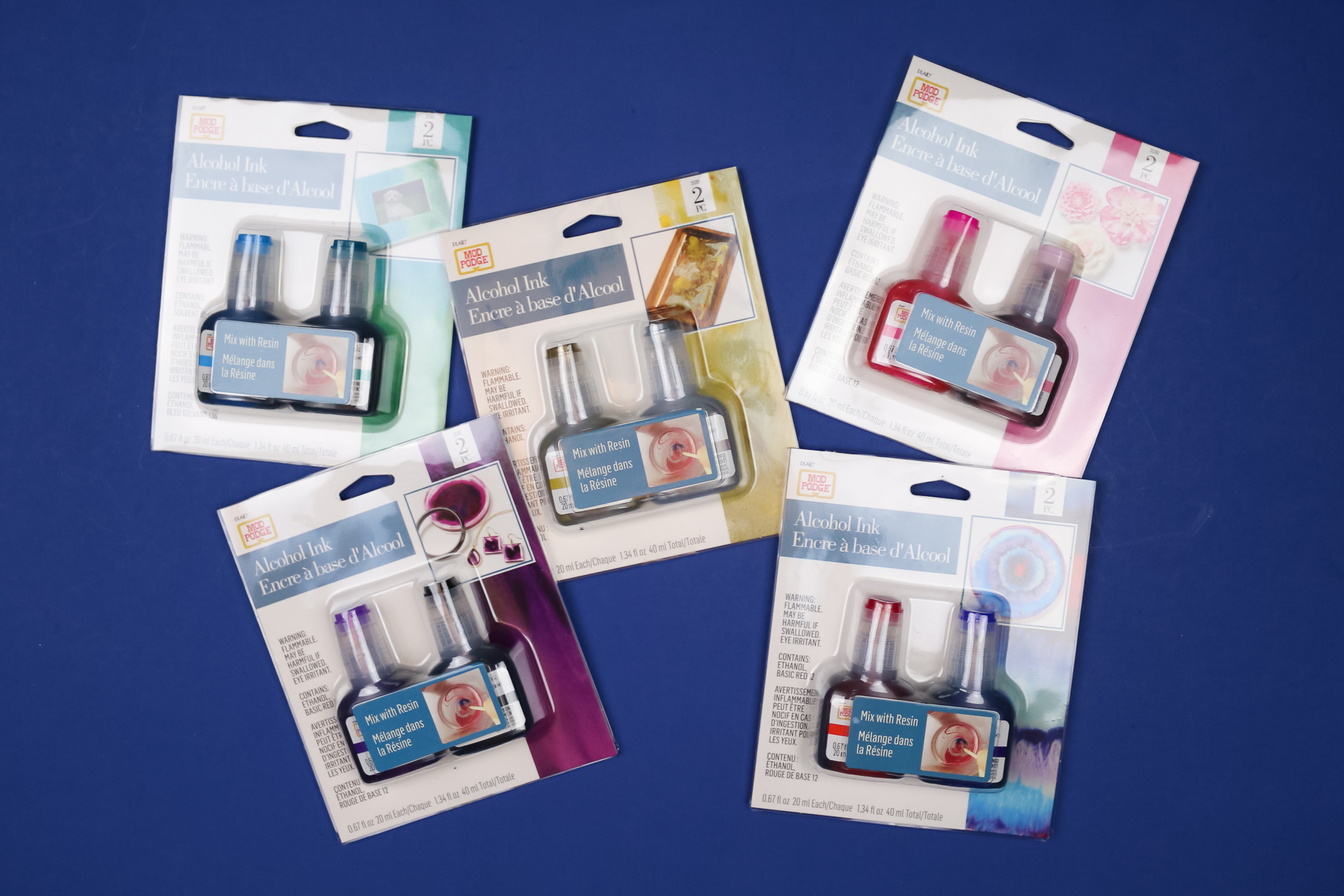 packages of Mod Podge alcohol ink on a blue background