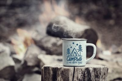 Camping is My Happy Place mug of hot steaming coffee sitting on an old log