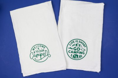two tea towels with camping designs in green vinyl