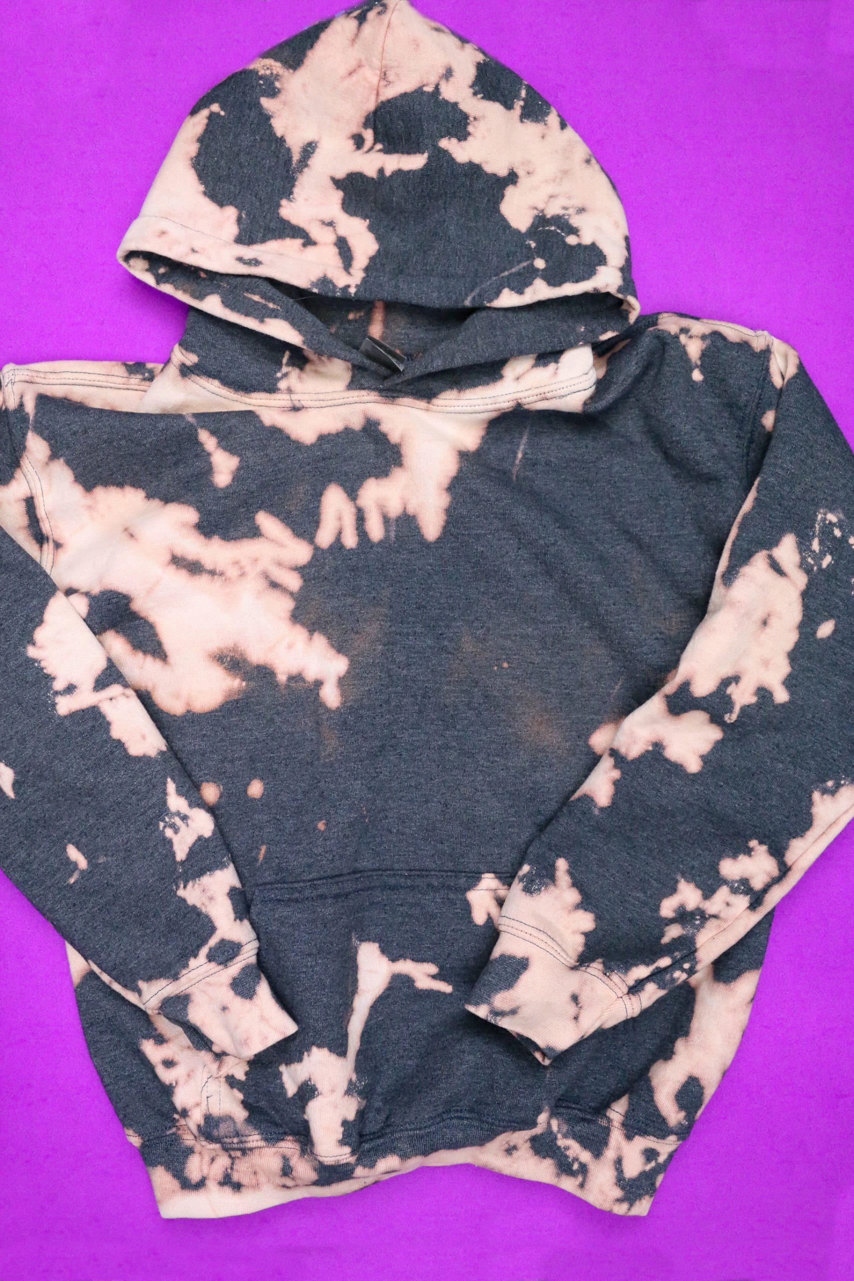 Grey bleach dyed sweatshirt on purple background