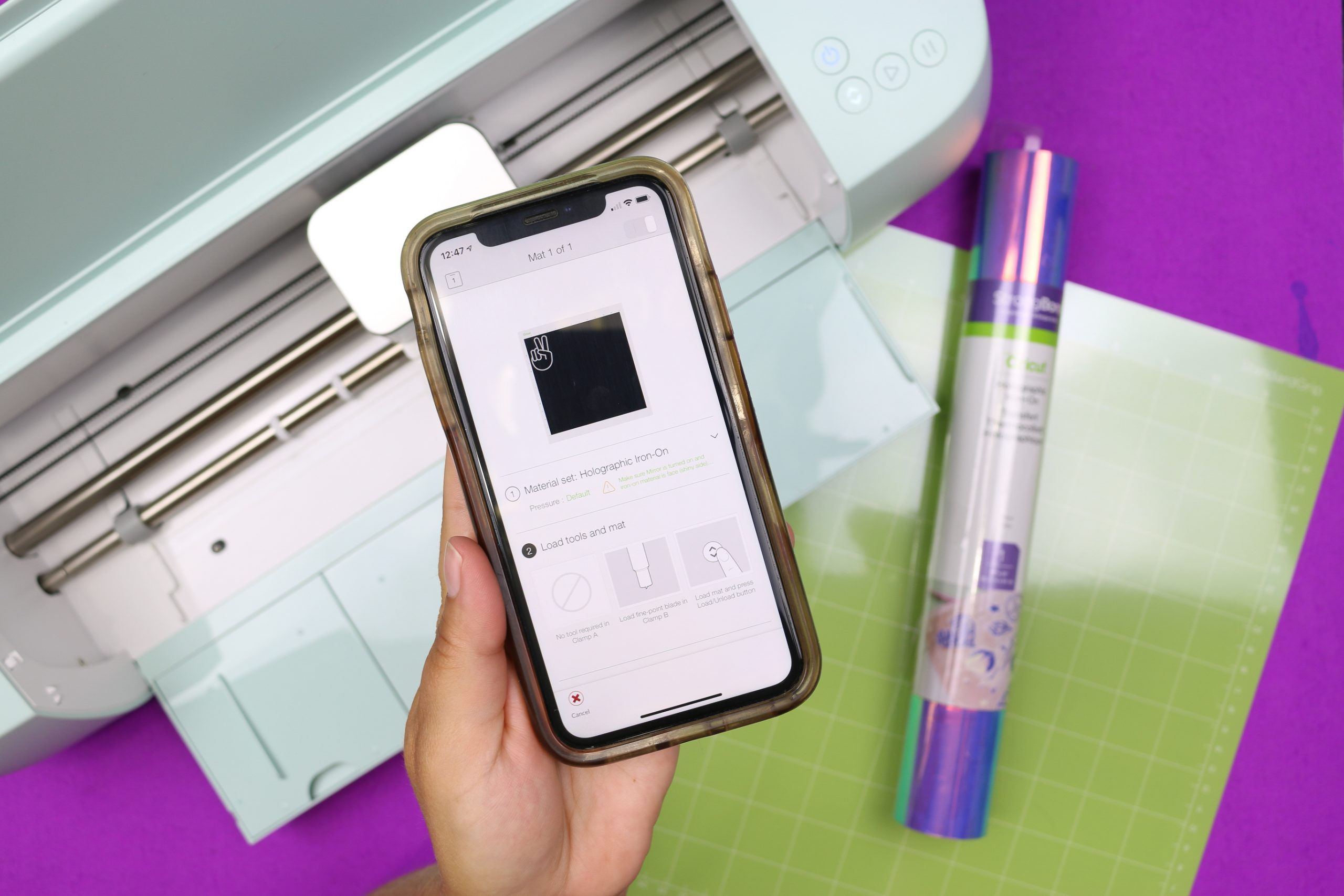 hand holding a smartphone displaying Cricut Design Space