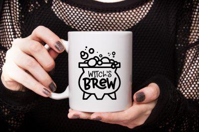 hand holding Witch's Brew mug