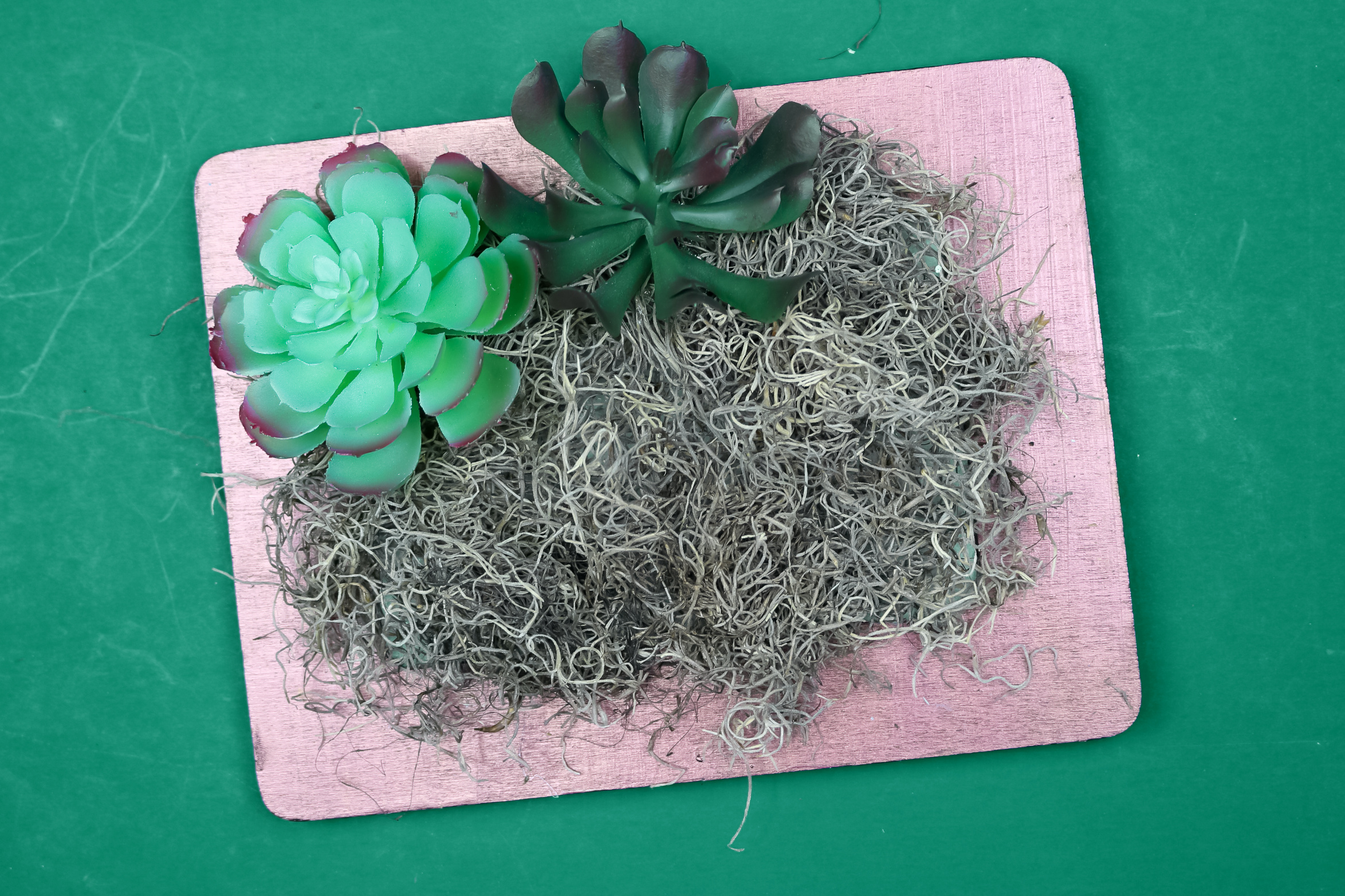 faux succulents glued to moss in a copper frame