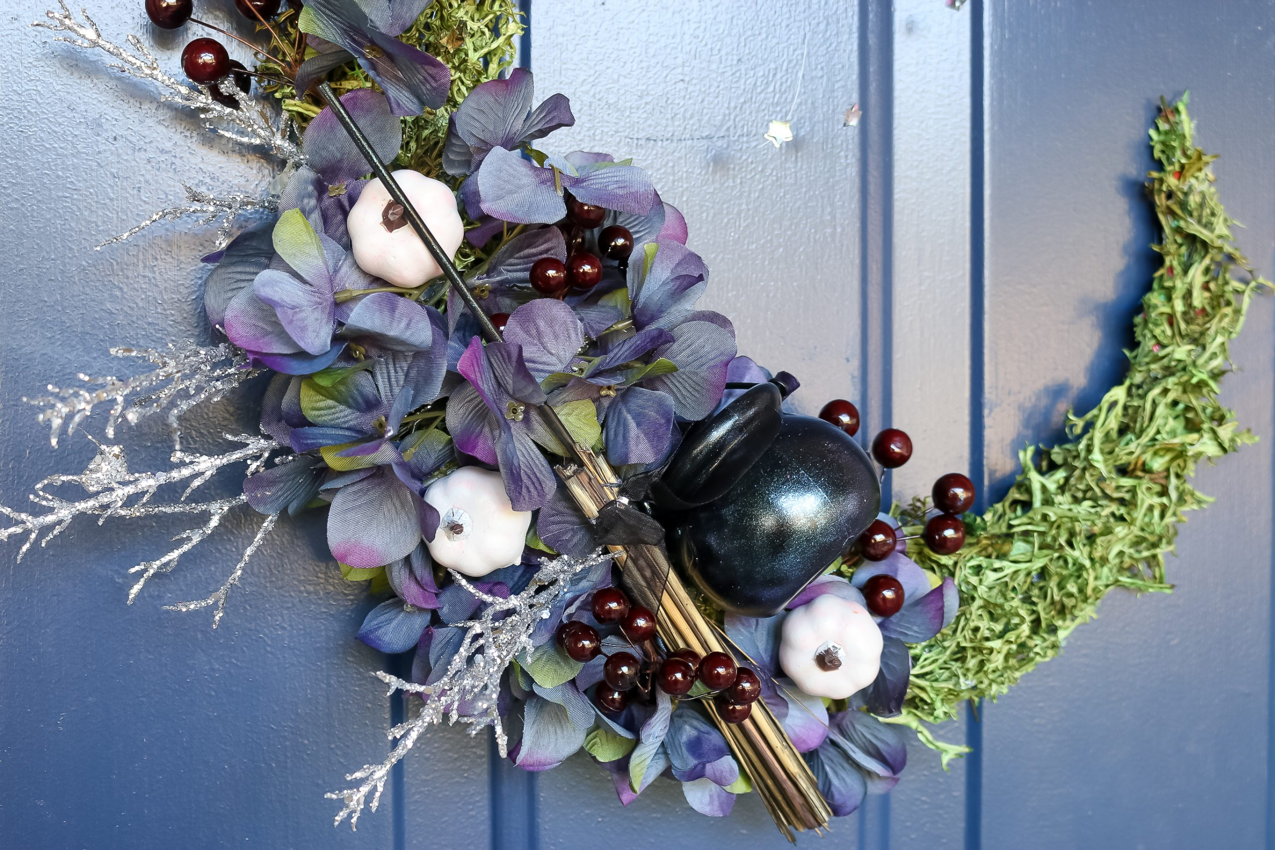 detail of floral crescent moon wreath on a blue door