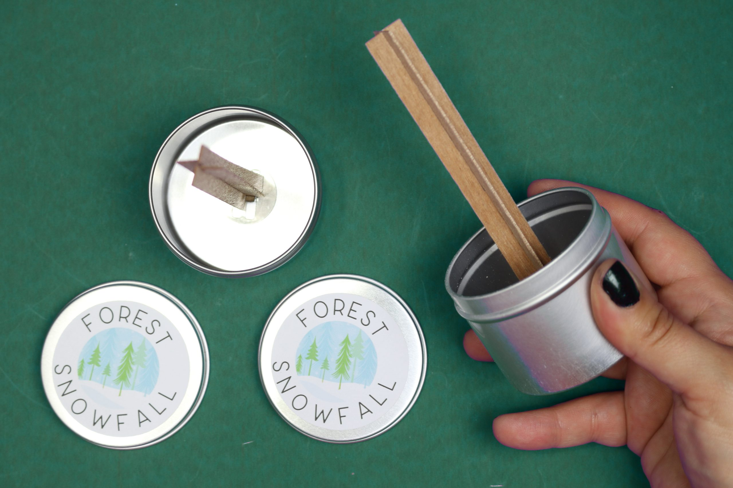 inserting wood wicks into candle tins