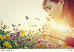 woman smelling flowers.