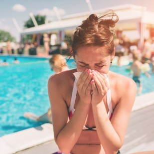 Woman experiencing allergies in the summer at the pool