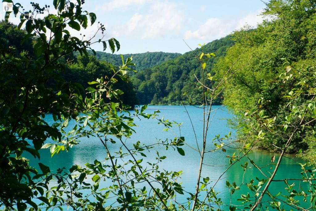 """Ausblick auf einen See im Nationalpark Plitvicer Seen - Kroatien   der See in der Mitte des Bildes wird von allen Seiten umrandet von diverser Pflanzenwelt und Bergen; links oben Text """"mado-unterwegs.com"""""""