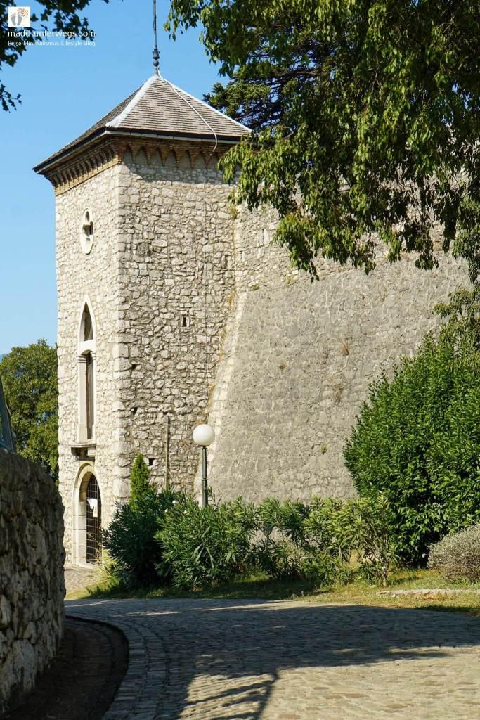 """Turm des Fort Trsat, vom rechten Rand ragen ein Baum und ein Busch in das Bild - Rijeka - Kroatien / links oben der Text """"mado-unterwegs.com"""""""