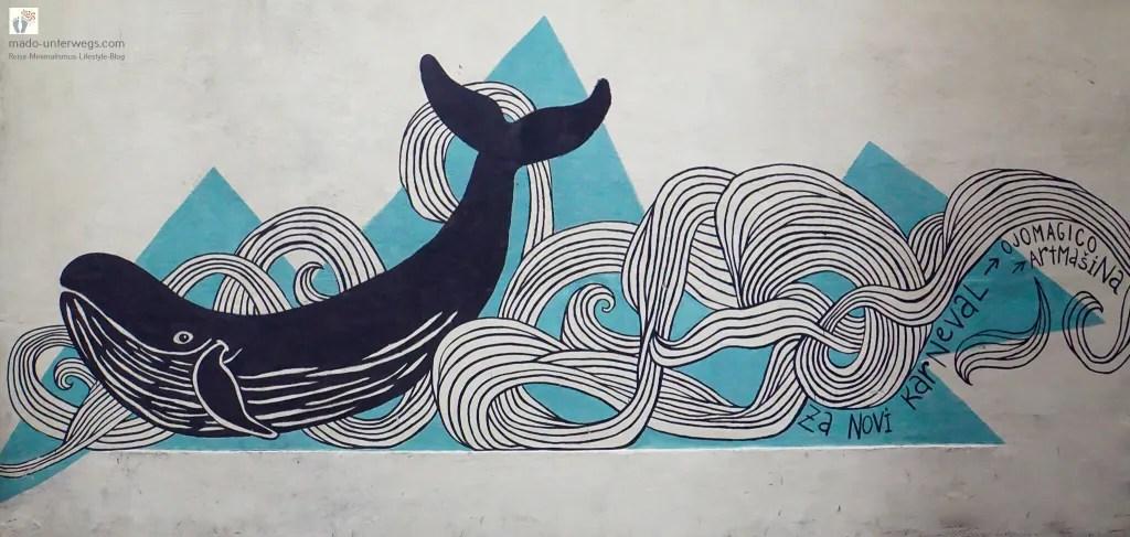 "Street-Art-Mural von Ojo Magico: dunkler Wal in straffierten Wellen, Titel ""Novi Karneval"" – in Rijeka - Kroatien / links oben der Text ""mado-unterwegs.com"""
