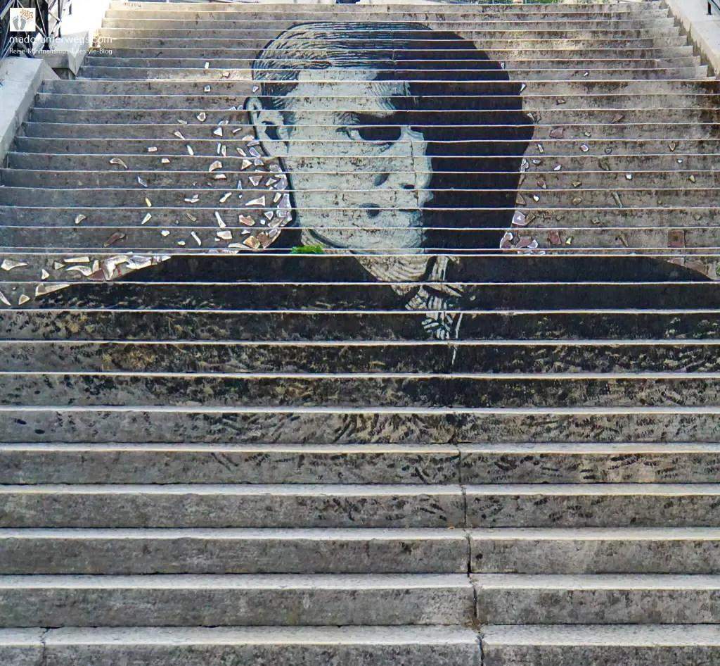 """Street-Art-Mural auf einer Treppe: Porträt von Josip Pičman - mit Glassteinen verziert – in Rijeka - Kroatien / links oben der Text """"mado-unterwegs.com"""""""