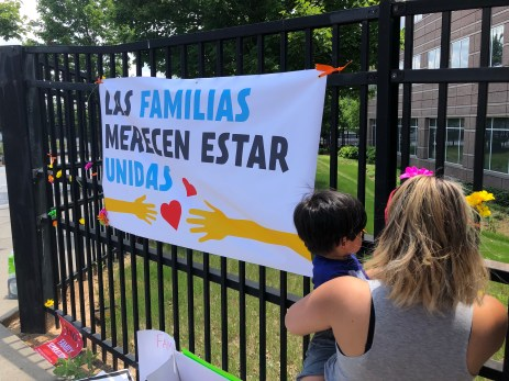White sign on black fence saying families belong together
