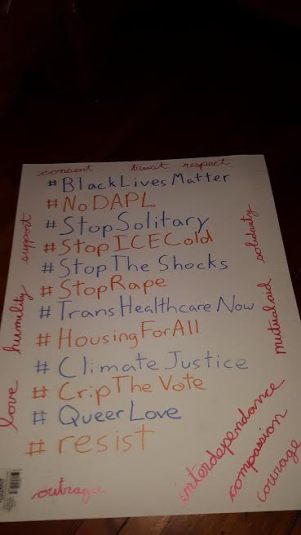 A sign with a bunch of hashtags in the middle:#BlackLivesMatter; #No DAPL; #StopSolitary; #StopICECold; #StopTheShocks; #StopRape; #TransHealthcareNow; #HousingForAll; #ClimateJustice; #CropTheVote; #QueerLove; #resist. Various words in cursive surround the hashtags, including love, humility, support, trust, outrage, mutual aid, solidarity, interdependence, compassion, and courage.