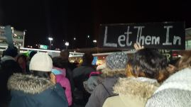 """A picture of a bunch of people dressed warmly protesting. The most prominent sign reads """"Let Them In"""""""