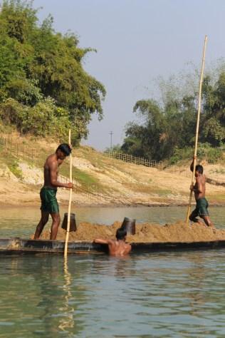 Bangladeshi men fish for sand from India.