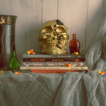 A promotional photo of the 2020 Halloween Book Bundle. From left to right: A goblet with a dragon for a handle has whisps of vapor trailing down its side. Next to it is a little green bottle, also dripping vapor. A gold skull and small red bottle sit on top of a stack of books that are in the bundle. Next to that is a gold statue of a cat. All of this sits infront of white wood panellin with a grey cheese cloth artfully draped across it. Candy corn is sprinkled around the image.