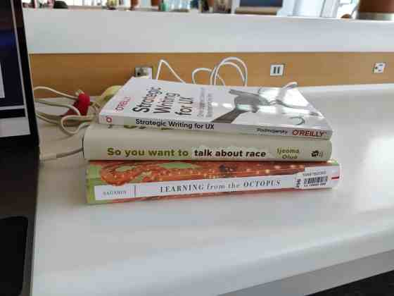 A stack of my three favorite books featured in this blog post with electrical cables behind them, and the surrounding context of an airport terminal.