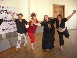 Vier Frauen der ARGE Dicke Weiber posieren beim Workshop für die Kamera, lachend und die Arme zur Kamera gestreckt, auf einem Bein stehend