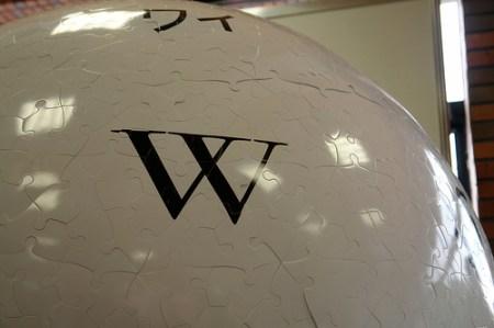 Der obere Teil eines weißen Balls aus Puzzleteilen, in der Mitte ein großes W (aus dem Wikipedia-Logo)